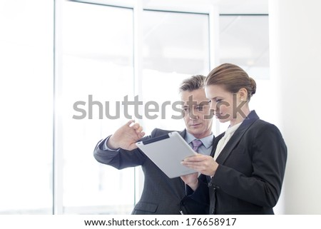 Businessman using tablet PC with female colleague in office - stock photo
