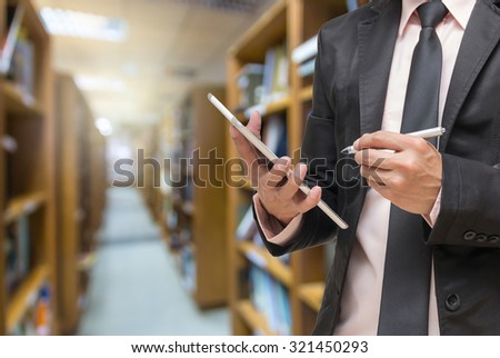 Businessman using the laptop with coffee cup on the Abstract blurred photo of library background - stock photo