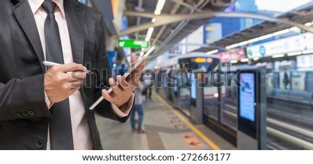 Businessman using the tablet on Abstract blurred photo of sky train station with people background - stock photo