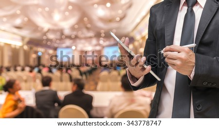 Businessman using the tablet on the Abstract blurred photo of conference hall or seminar room with attendee background - stock photo