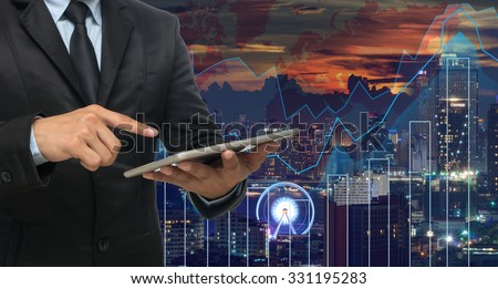 businessman using the tablet on Trading graph on the cityscape at night and world map background,Business financial concept - stock photo