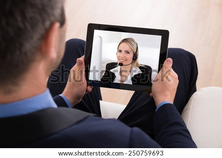 Businessman Video Conferencing With Businesswoman On Digital Tablet - stock photo
