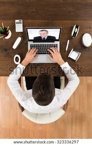 Businessman Videochatting Online With Senior Colleague On Laptop At Desk - stock photo