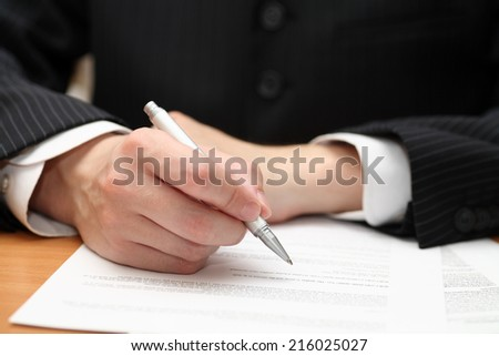 Businessman viewing the contract before signing. - stock photo