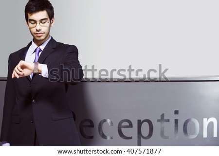 Businessman waiting at office reception, looking at his watch - stock photo