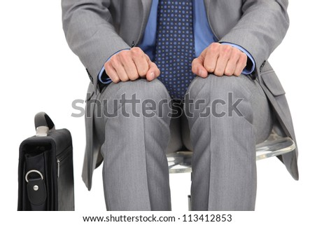 businessman waiting at station with briefcase by his side - stock photo