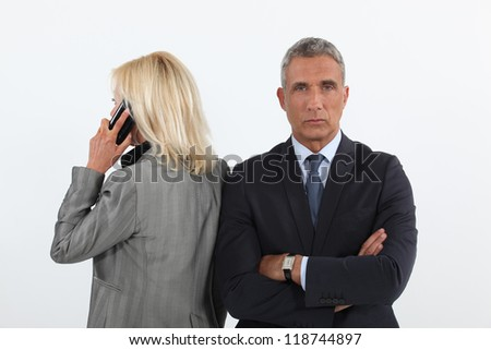 businessman waiting while his colleague is talking on her cell - stock photo