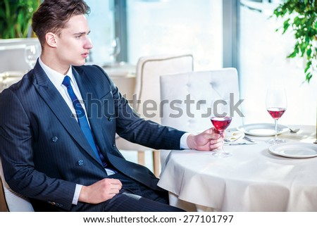Businessman waits for the main meeting. Confident businessman in formal wear sitting at a table in a restaurant while holding a glass of wine and looking away - stock photo