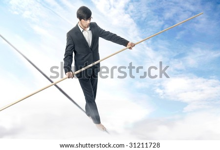 Businessman walking a tightrope - stock photo