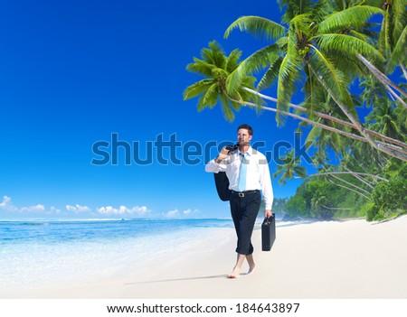 Businessman Walking Along a Tropical Beach - stock photo