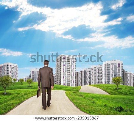 Businessman walking along road running through green hills with a few trees. High-rise buildings as backdrop - stock photo