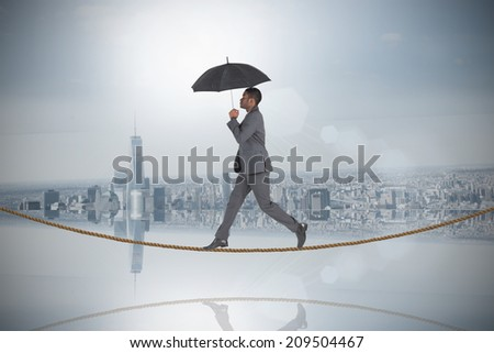 Businessman walking and holding umbrella on tightrope against room with large window looking on city - stock photo