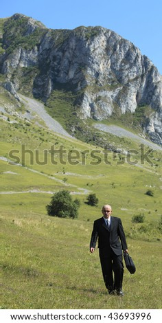 Businessman walking in a mountaineous area. - stock photo