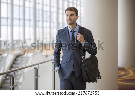 Businessman walking in the office corridor with briefcase - stock photo