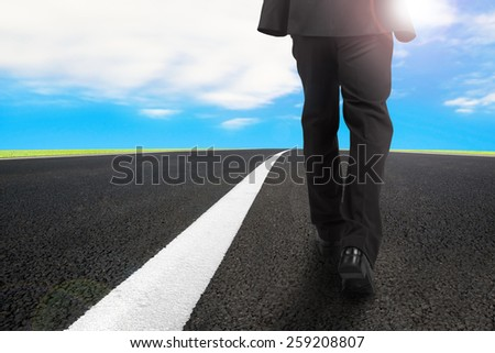 Businessman walking on asphalt road with white line and sunlight blue sky - stock photo