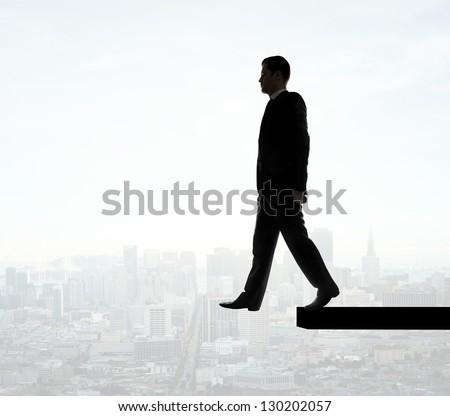 businessman walking on edge of city on background - stock photo
