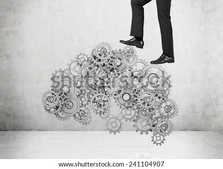 businessman walking on silver gears and cogs - stock photo