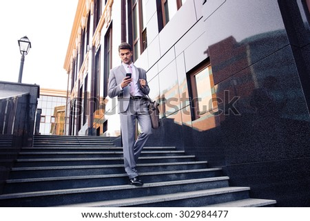 Businessman walking on the stairs and using smartphone outdoors - stock photo
