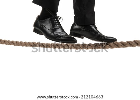 businessman walking on tightrope on white background. businessman trying to keep his balance isolated on white background - stock photo