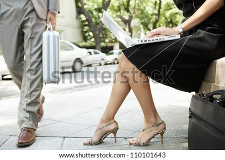 Businessman walking passed a sexy businesswoman who's using her laptop computer while sitting down outdoors. - stock photo