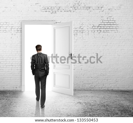 businessman walking to opened loft door - stock photo