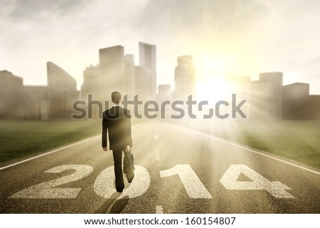 Businessman walking to the New Year 2014 with cityscape background - stock photo