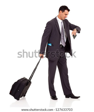 businessman walking with trolley bag and looking at his watch - stock photo