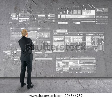 businessman watching business plan on wall  - stock photo