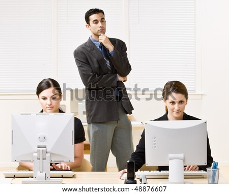 Businessman watching co-workers work - stock photo
