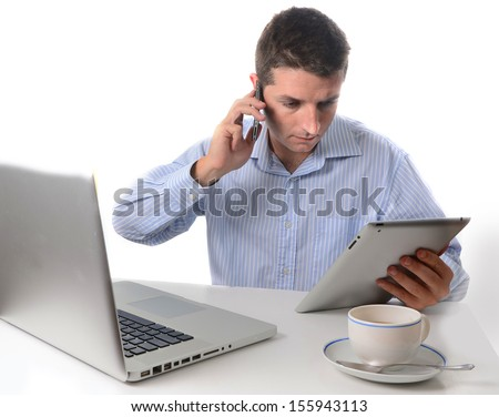 Businessman wearing a blue business shirt multi-tasking speaking on a smart phone holding a tablet and sitting in front of a laptop on a white background - stock photo