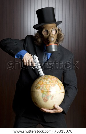 Businessman wearing a gas mask holding a gun to an earth globe - stock photo