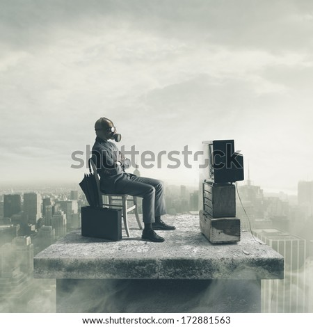 Businessman wearing a gas mask watching TV - stock photo