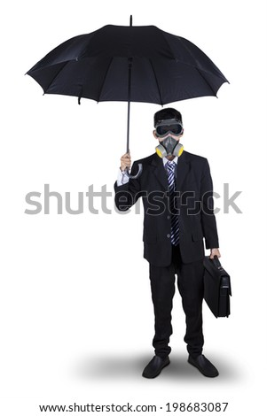 Businessman wearing a gas mask while holding an umbrella and briefcase. Isolated on white background - stock photo