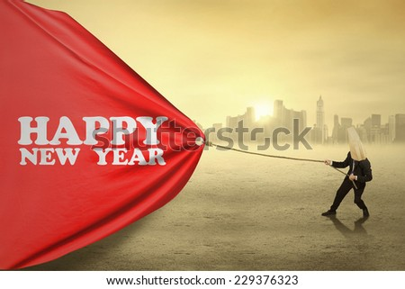 Businessman wearing a mask and pull a big banner of new year - stock photo