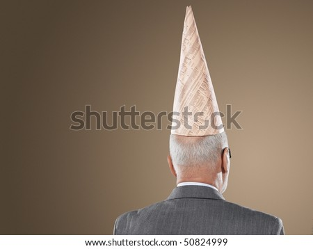 Businessman Wearing Dunce hat, back view, head and shoulders - stock photo