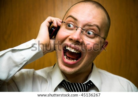 businessman wearing glasses emotional shouting on his cell phone - stock photo