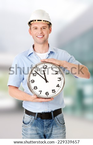 Businessman wearing helmet holding a clock - stock photo