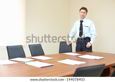 Businessman wearing white shirt stands near table in empty meeting room. - stock photo