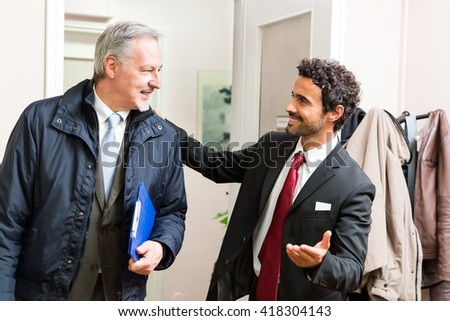 Businessman welcoming a colleague - stock photo