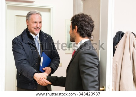 Businessman welcoming a guest in his office - stock photo