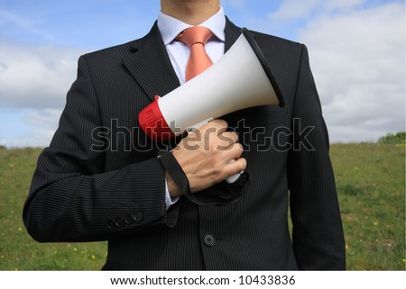 Businessman with a black suit holding a megaphone like gun - stock photo