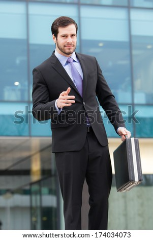 businessman with a briefcase in front of an office building  - stock photo