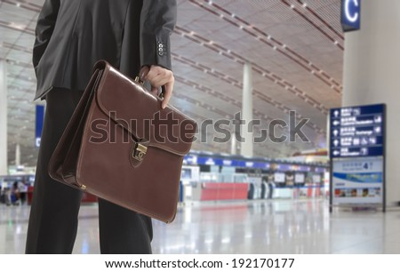 Businessman with a briefcase on a background of airport - stock photo