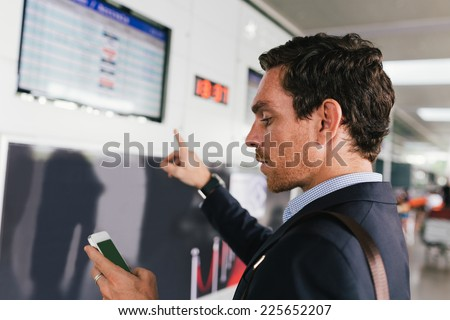 Businessman with a cellphone and pointing at the airline schedule - stock photo