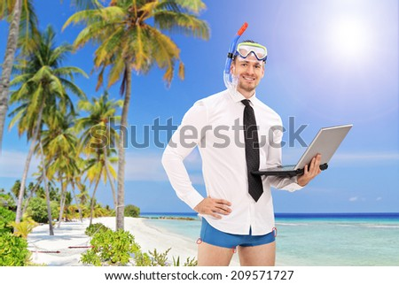 Businessman with a diving mask holding a laptop and standing on a beach with palm trees - stock photo