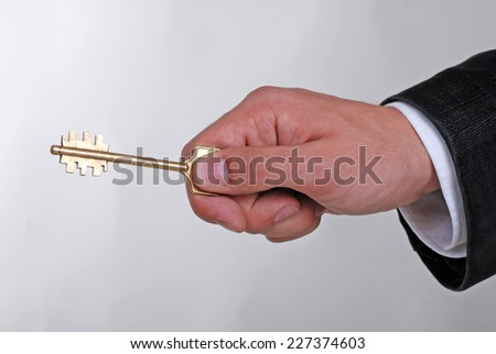 Businessman with a golden key in his hand on grey background - stock photo