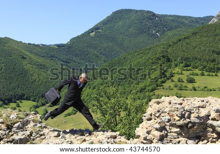 Businessman with a laptop bag running outdoors on a rocky ruined stronghold wall in a mountainous area. - stock photo