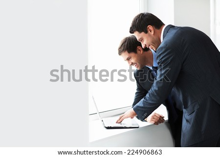 Businessman with a laptop by the window - stock photo