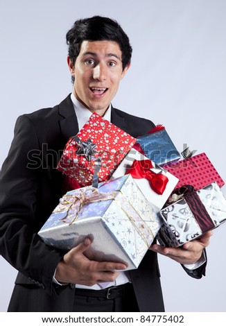 Businessman with a lot of gift packages (isolated on gray) - stock photo