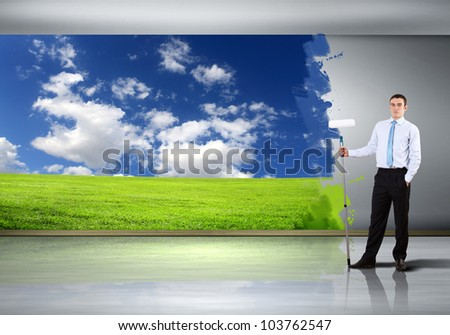 Businessman with a paint brush creating natural background - stock photo
